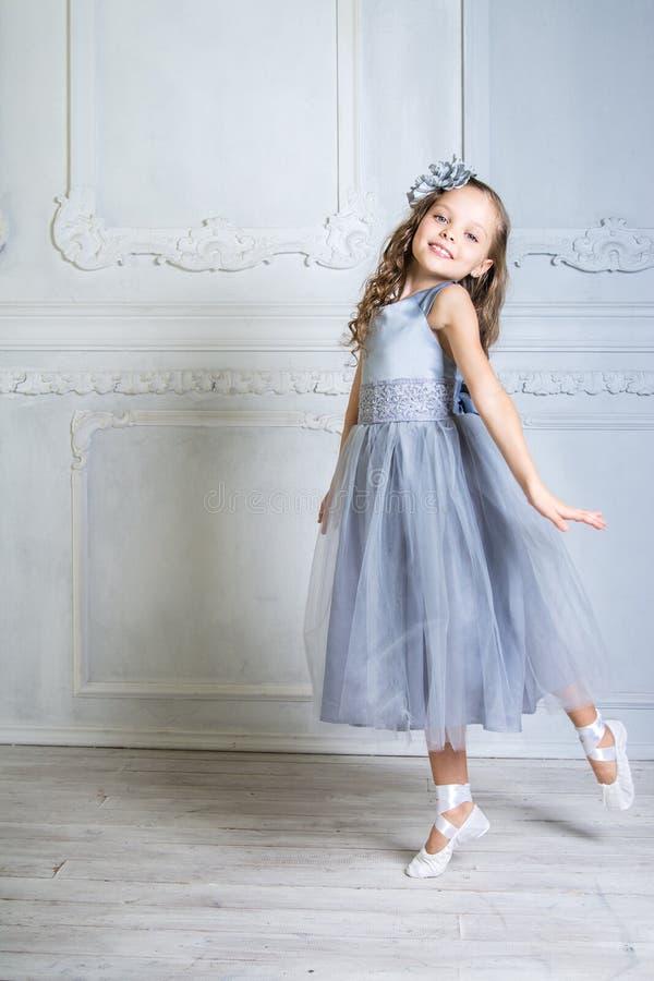 Schönes Mädchen in den grauen Kleider- und pointeschuhen wirft im r auf stockfoto
