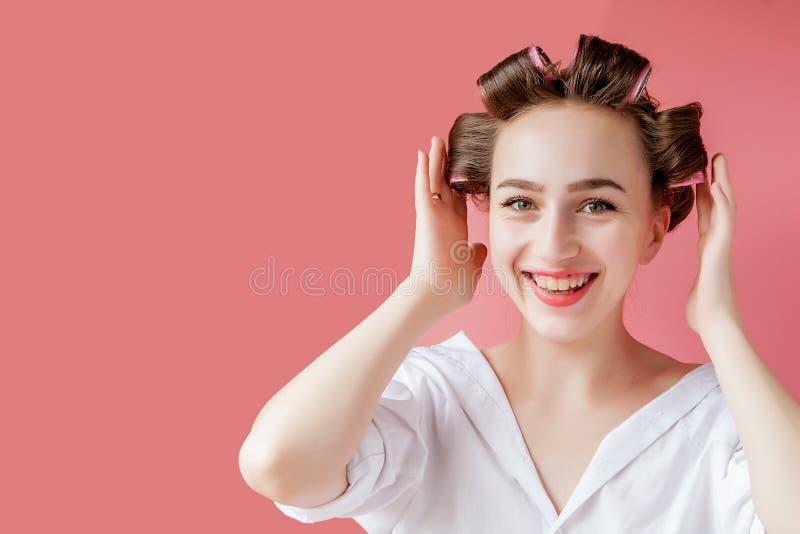 Schönes Mädchen in den Haarlockenwicklern auf rosa Hintergrund stockfotos