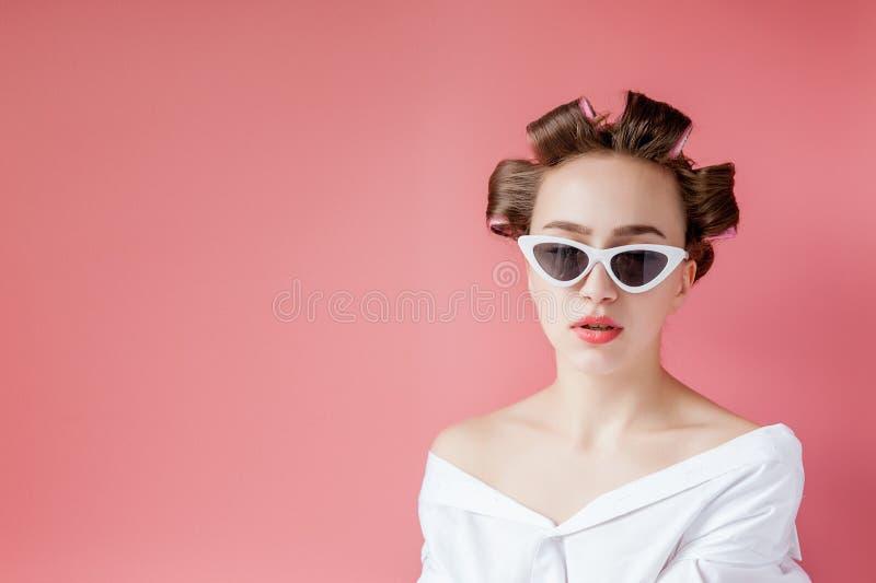 Schönes Mädchen in den Haarlockenwicklern auf rosa Hintergrund stockfoto