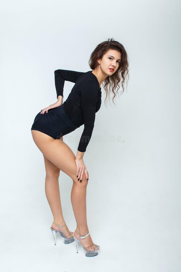 Schönes Mädchen in den hohen Absätzen in der schwarzen Kleidung für das Tanzen Bloße Beine mit glatter Haut Auf Tabelle ist ein b lizenzfreie stockbilder