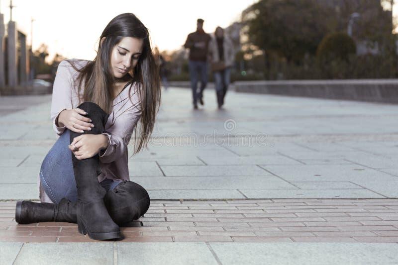 Schönes Mädchen in den Stiefeln, die auf dem Boden sitzen stockfoto