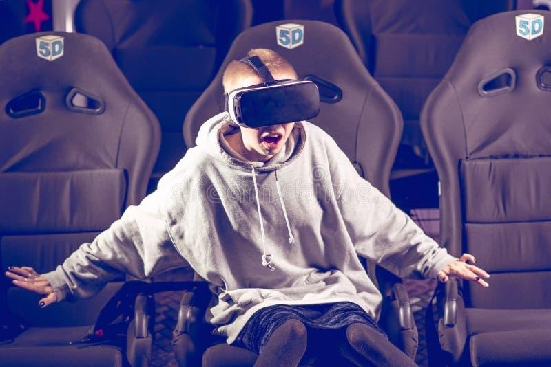 Schönes Mädchen in den virtuellen Gläsern passt einen Film mit Spezialeffekten in 5d auf stockfotos