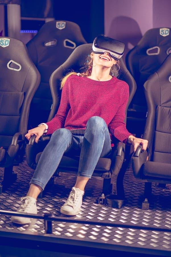 Schönes Mädchen in den virtuellen Gläsern passt einen Film mit Spezialeffekten in 5d auf lizenzfreies stockbild