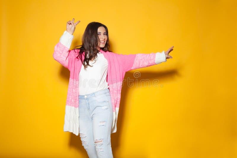 Schönes Mädchen in der bunten Kleidung, die auf einem Gelb aufwirft stockfoto