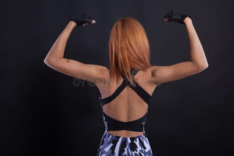 Schönes Mädchen der Eignung, das ihre Rückseite während Studio photoshoot biegt stockfotos