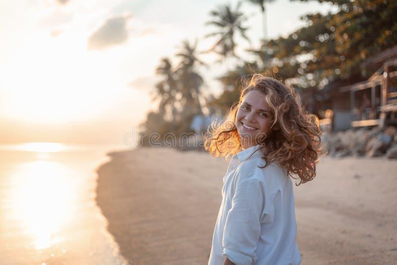 Schönes Mädchen der jungen Frau mit dem gelockten Haar des Fliegens auf dem Hintergrund eines tropischen Strandes bei Sonnenunter stockbild