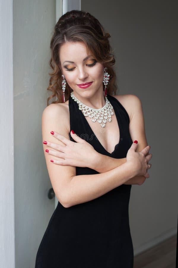 Schönes Mädchen in der schwarzen Abendkleidercocktailparty stockbilder