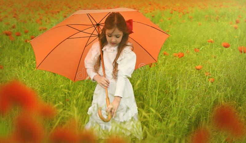 Schönes Mädchen in der weißen Kleiderstellung auf dem Mohnblumengebiet und -griffen ein Regenschirm lizenzfreie stockfotografie