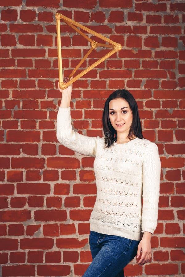Schönes Mädchen in der weißen Strickjacke hält hölzerne Dreieckpyramide in den Händen einer Backsteinmauer lizenzfreie stockfotografie