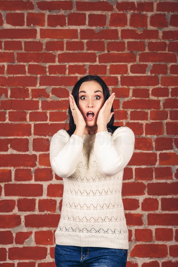 Schönes Mädchen in der weißen Strickjacke mit überraschtem Blick und ein offener Mund gegen Backsteinmauerhintergrund lizenzfreies stockbild