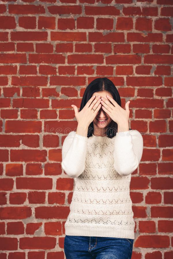 Schönes Mädchen in der weißen Strickjacke schließt ihre Augen mit ihren Händen gegen Hintergrund der Backsteinmauer Kopieren Sie  lizenzfreie stockfotos