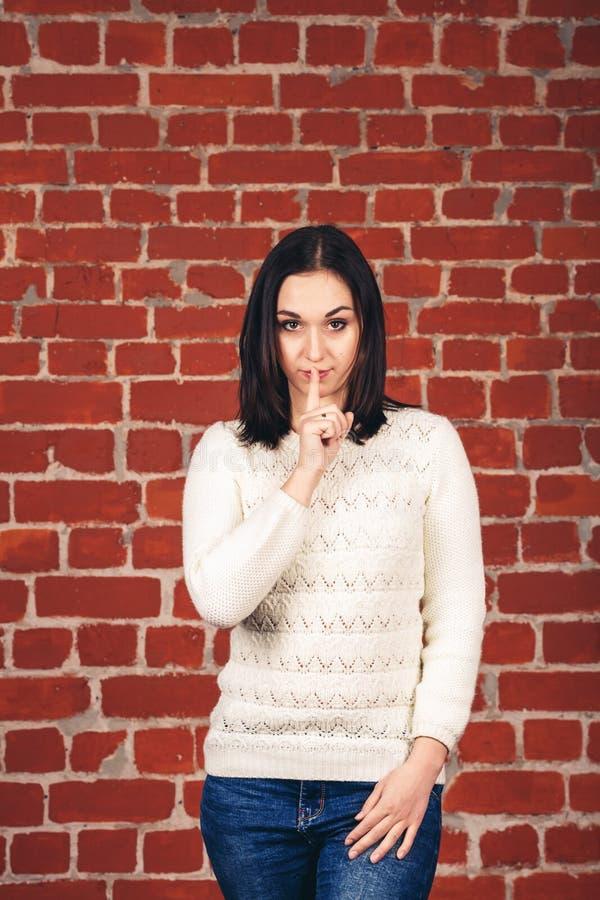 Schönes Mädchen in der weißen tuenden Strickjacke shh auf Backsteinmauerhintergrund Kopieren Sie Platz stockbild