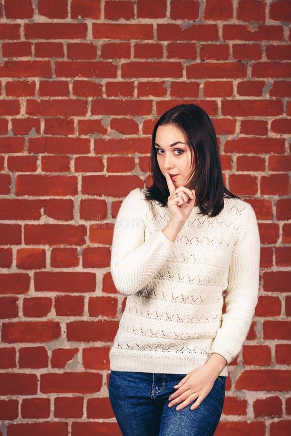 Schönes Mädchen in der weißen tuenden Strickjacke shh auf Backsteinmauerhintergrund Kopieren Sie Platz stockfoto