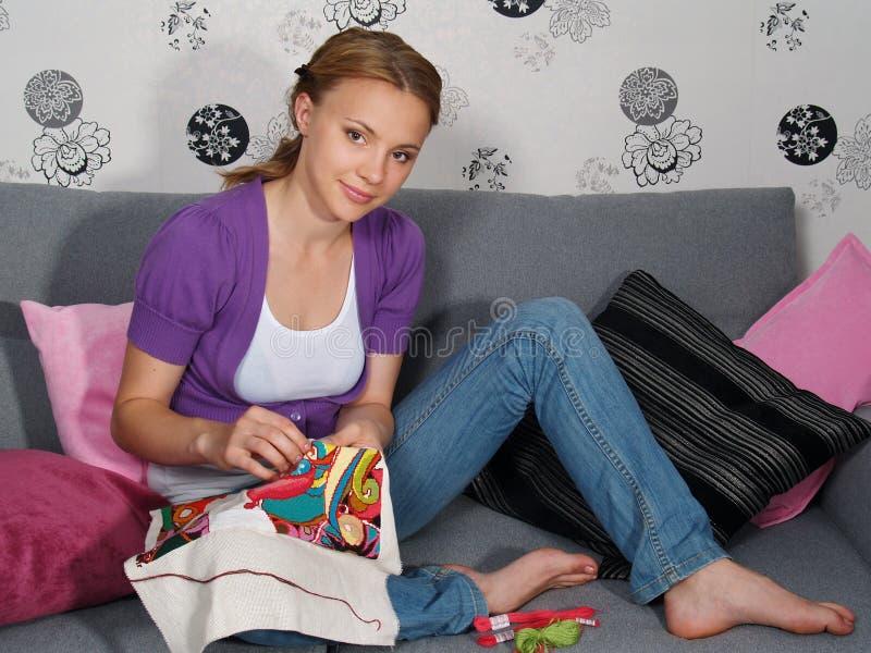 Schönes Mädchen in der Wohnung stickt stockfoto