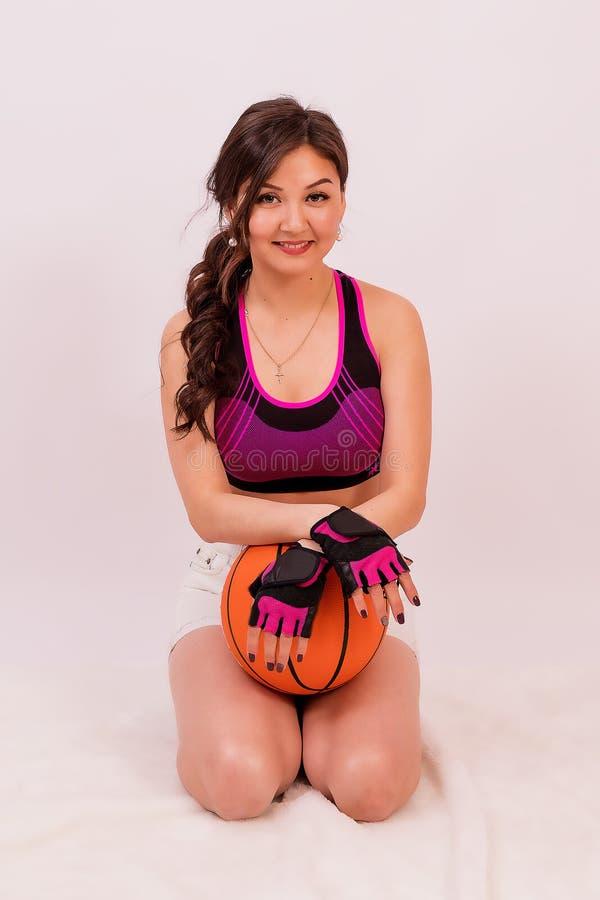 Schönes Mädchen des asiatischen Auftrittes ankleidend für einen Sport mit einem Ball für Spiel im Basketball stockfoto
