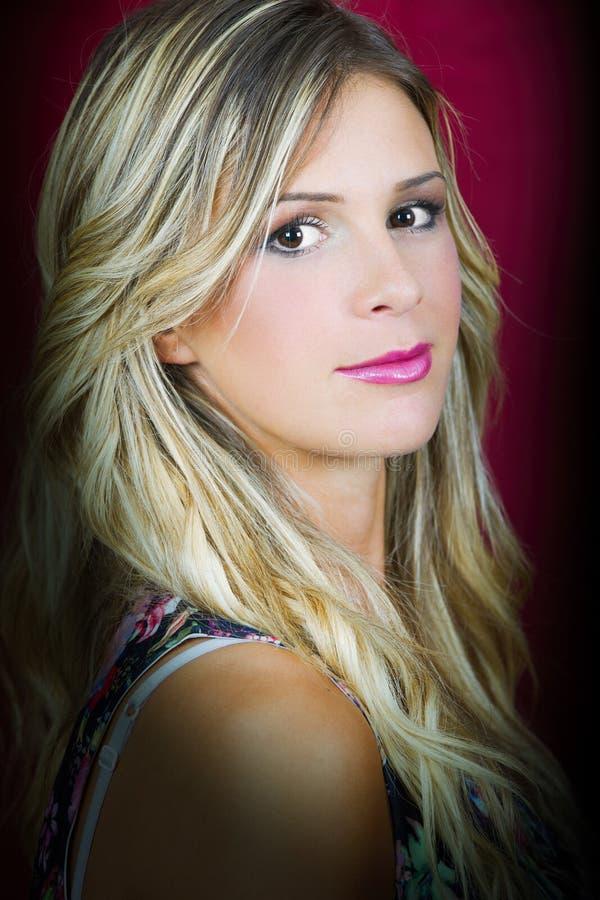 Schönes Mädchen des blonden Haares des Porträts mit Make-up und rotem Hintergrund stockbilder