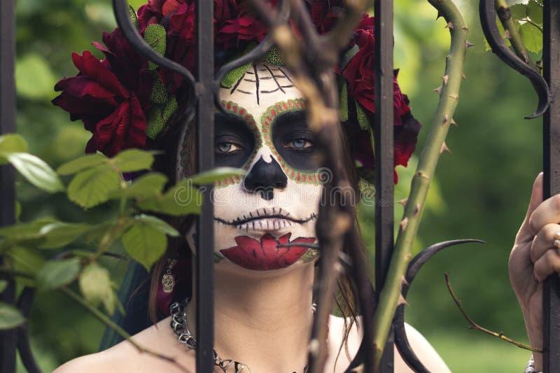Schönes Mädchen des nahen hohen Porträts Make-up im traditionellen Mexikaner Calavera-Zuckerschädel auf dem Hintergrund eines Eis stockbild