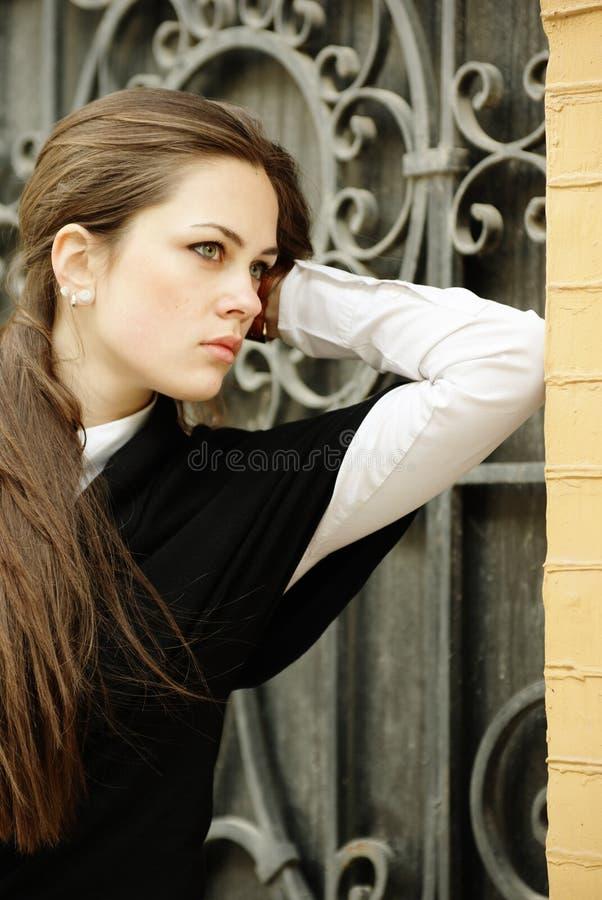 Schönes Mädchen durch die geschmiedeten Gatter stockfotos