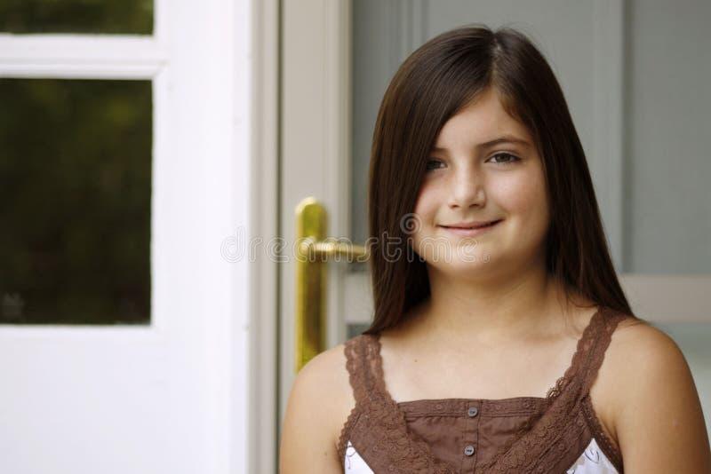 Schönes Mädchen durch Door lizenzfreies stockbild