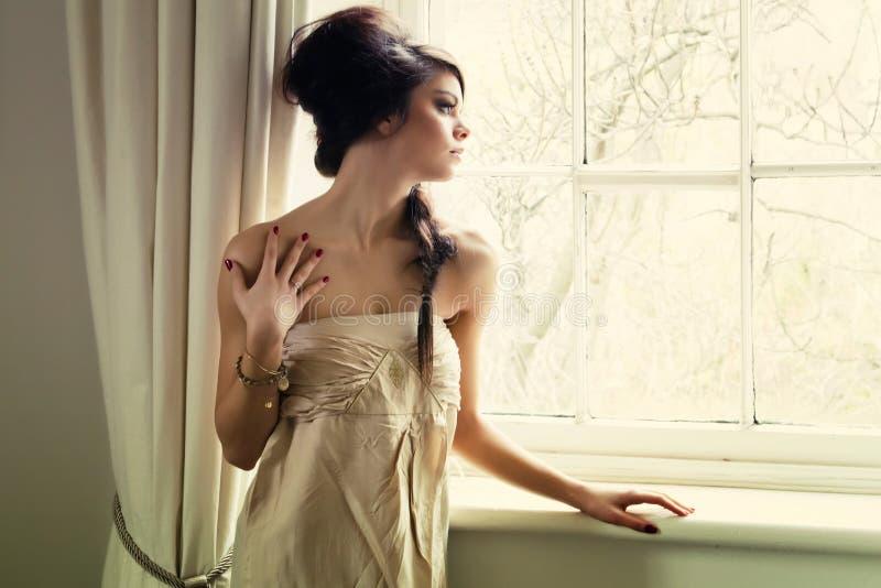 Schönes Mädchen durch Fenster lizenzfreies stockfoto