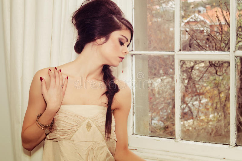Schönes Mädchen durch Fenster stockbild