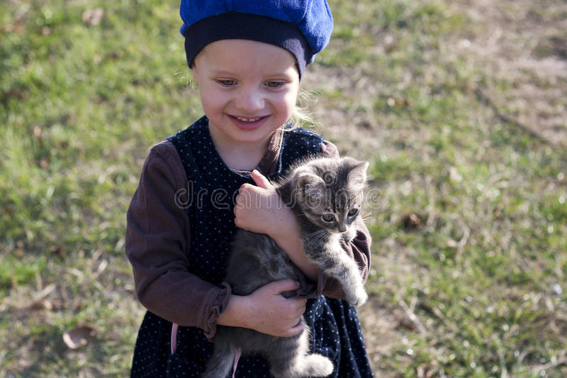 Schönes Mädchen in einem Barett mit einem grauen Kätzchen auf seinen Händen lizenzfreies stockbild