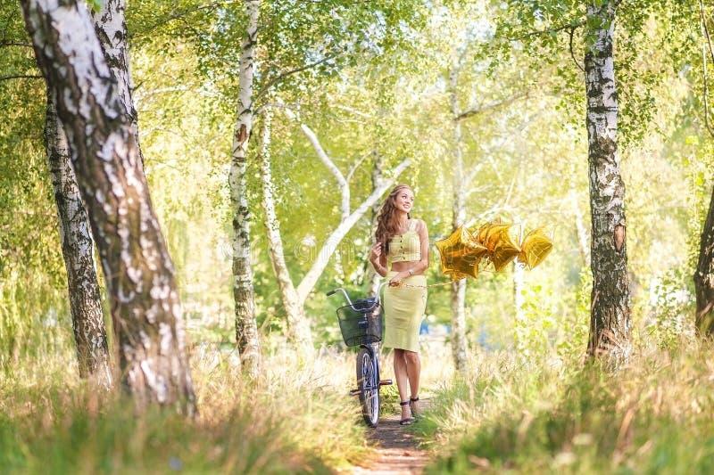 Schönes Mädchen in einem gelben Rock und Spitze mit einem Fahrrad auf einem Weg im Sommer Frau auf einem Datum im Wald auf einem  stockfoto