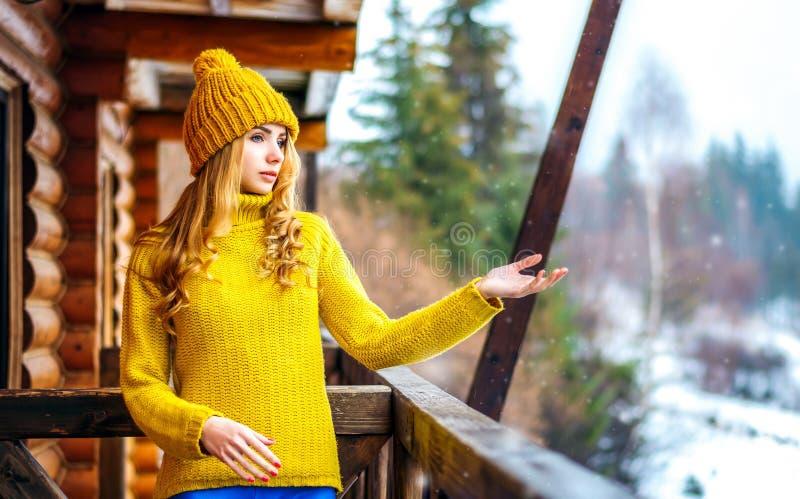 Schönes Mädchen in einem gelben Strickpulli und in einem Hut fängt die Schneehände und -blick lizenzfreie stockfotos
