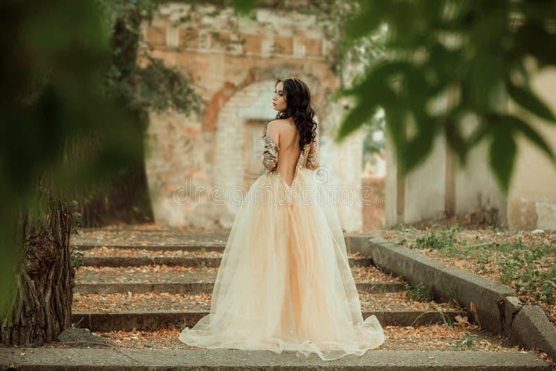 Schönes Mädchen in einem Gold, luxuriöses Kleid stockbild