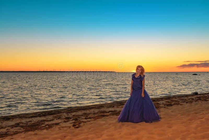 Schönes Mädchen in einem hellen violetten Kleid durch das Meer lizenzfreie stockfotografie