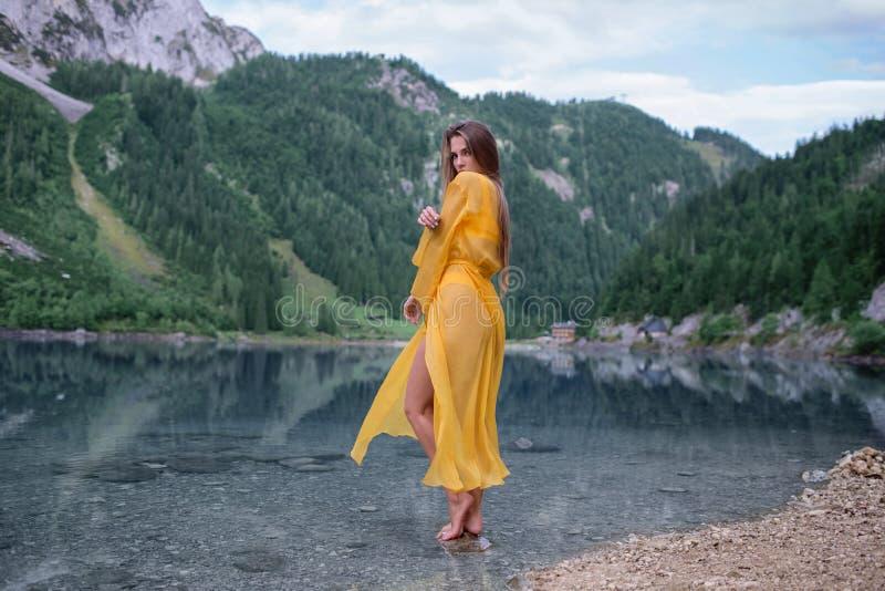 Schönes Mädchen in einem hellgelben Kleid auf einem See in den Bergen lizenzfreie stockfotografie