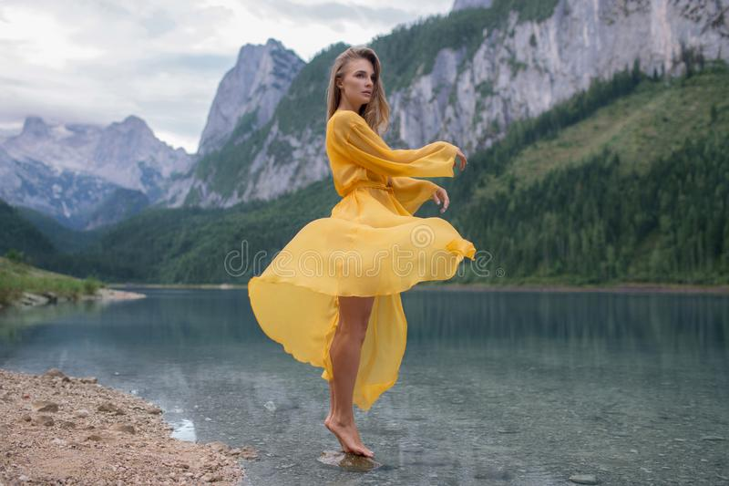 Schönes Mädchen in einem hellgelben Kleid auf einem See in den Bergen lizenzfreie stockfotos