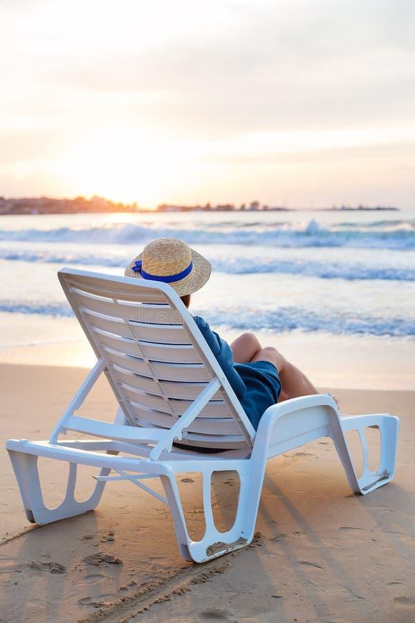 Schönes Mädchen in einem Hut sitzt auf einem deckchair, welches die Dämmerung trifft stockfotografie