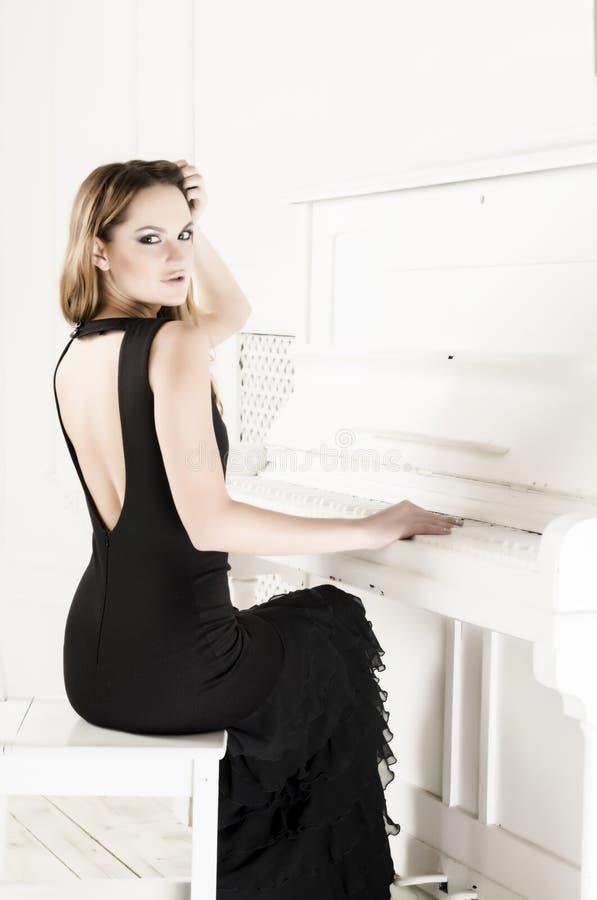 Schönes Mädchen in einem langen Kleid mit dem offenen Rücken, der am Klavier sitzt stockbilder