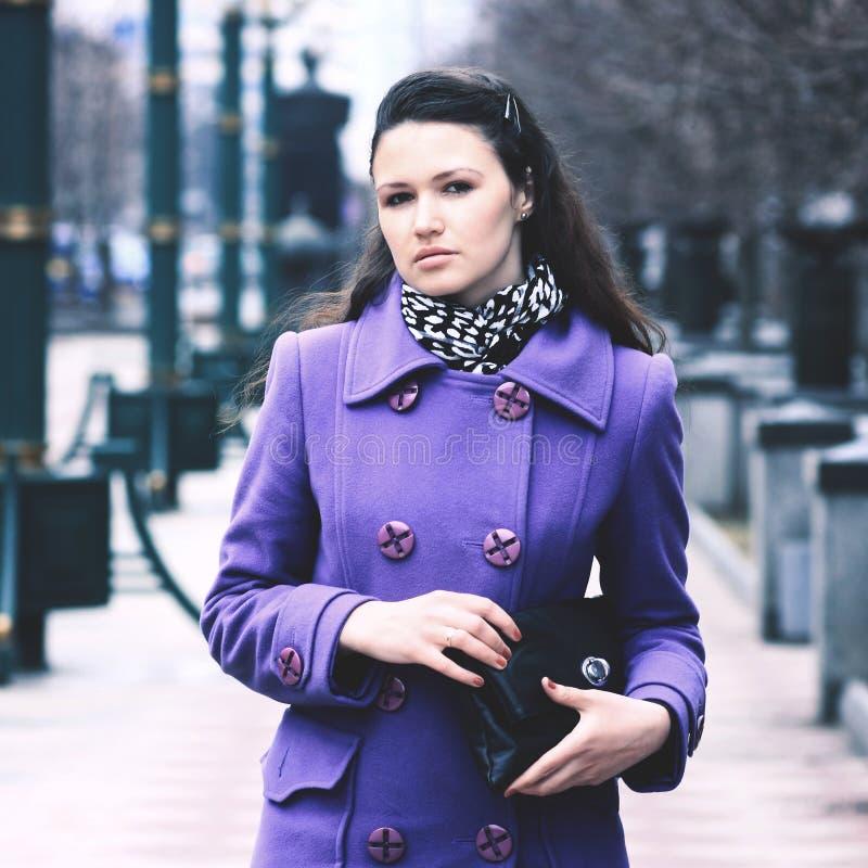 Schönes Mädchen in einem Mantel auf der Straße mit einer Tasche lizenzfreie stockfotografie