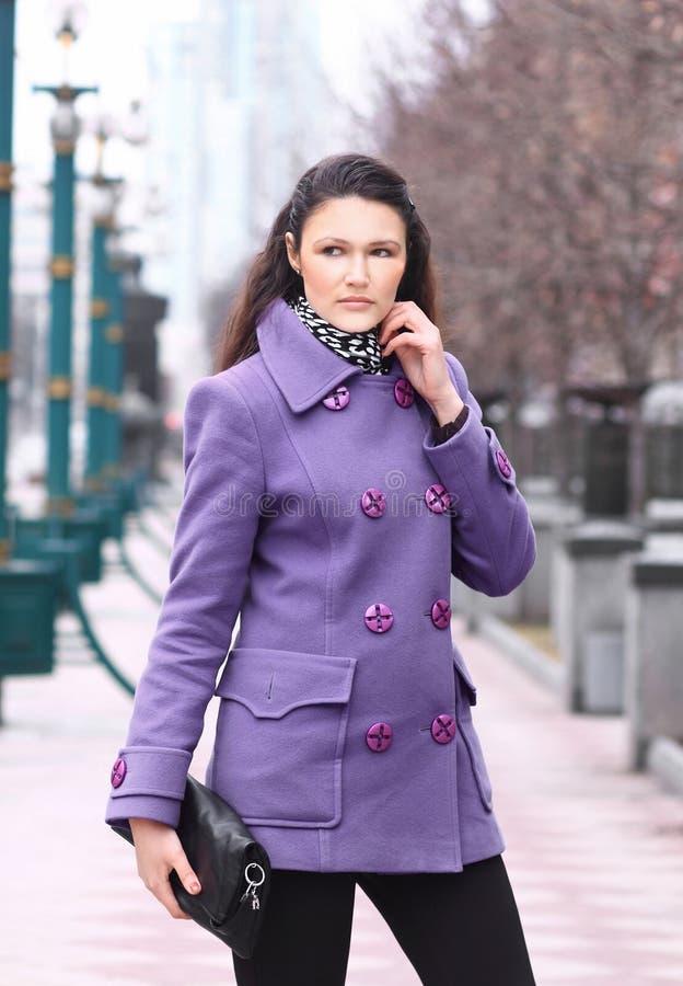 Schönes Mädchen in einem Mantel im Park mit einer Kupplung in ihren Händen lizenzfreie stockbilder