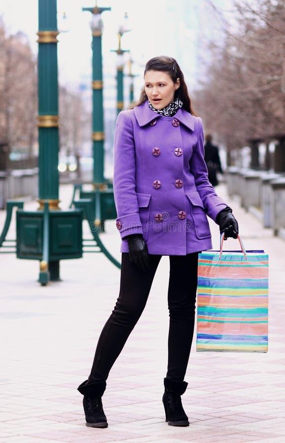 Schönes Mädchen in einem Mantel mit dem Einkaufen auf der Straße lizenzfreie stockfotografie