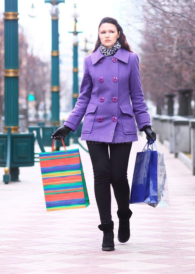 Schönes Mädchen in einem Mantel mit dem Einkaufen auf der Straße lizenzfreie stockbilder