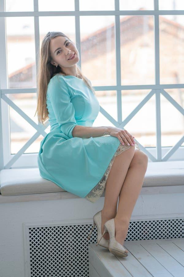 Schönes Mädchen in einem netten Kleid, das am Fenster auf dem Fensterbrett am Nachmittag sitzt stockfotos