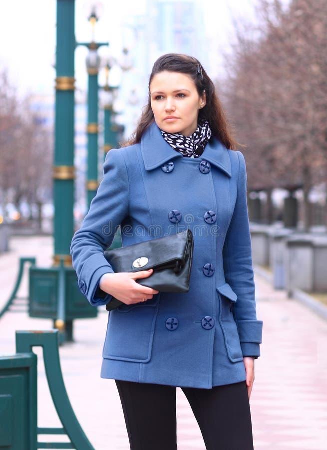Schönes Mädchen in einem purpurroten Mantel im Park mit einer Kupplung in ihren Händen stockfoto