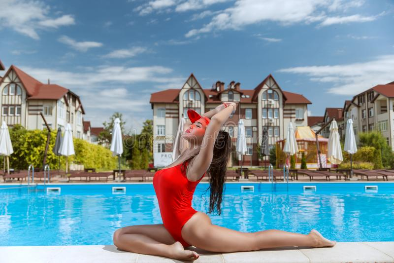 Schönes Mädchen in einem roten Badeanzug in einem schönen Hotel nahe dem Pool stockbild
