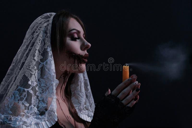 Schönes Mädchen in einem schrecklichen Nonnenkostüm brennt heraus die Kerze durch Frauenportr?t mit Halloween-Make-up Konzept f?r stockfoto