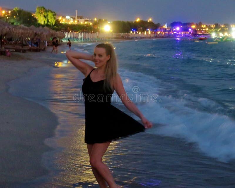 Schönes Mädchen in einem schwarzen Kleid durch das Meer stockbilder