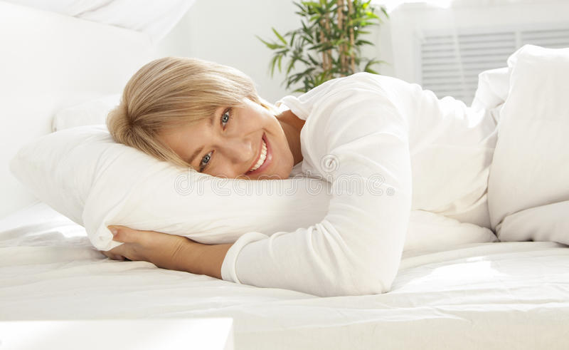 Schönes Mädchen in einem weißen Bett morgens, lächelnd stockfoto