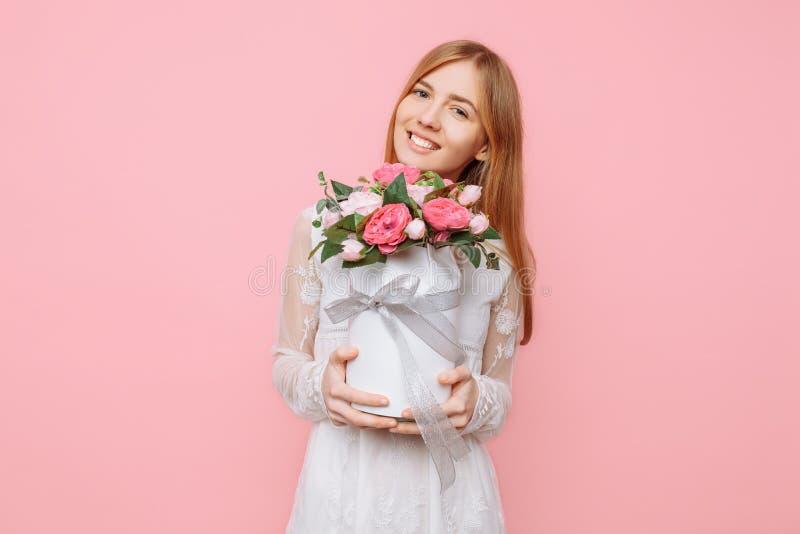 Schönes Mädchen in einem weißen Kleid, steht mit einem Blumenstrauß von Pfingstrosen, auf einem rosa Hintergrund 8. März Konzept lizenzfreies stockbild