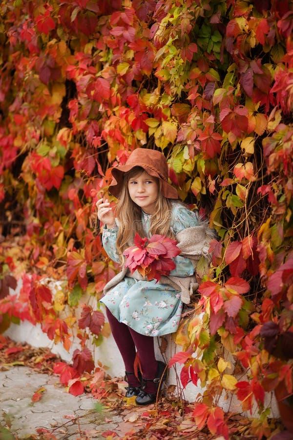 Schönes Mädchen in einem Weinlesekleid und in einem Hut im Herbstgarten, eine Wand von roten Blättern lizenzfreies stockbild