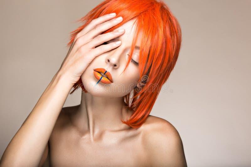 Schönes Mädchen in einer cosplay Art der orange Perücke mit den hellen kreativen Lippen Kunstschönheitsbild lizenzfreies stockbild