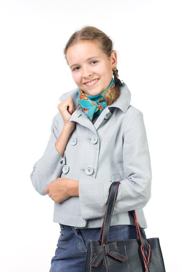 Schönes Mädchen in einer Jacke mit einem Beutel lizenzfreies stockbild
