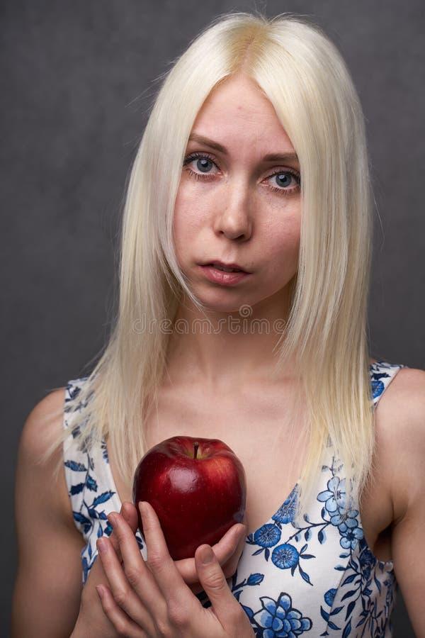 Schönes Mädchen in einer modischen Kleidung mit Apfel stockfoto