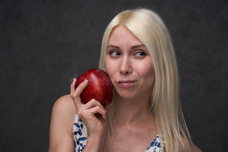 Schönes Mädchen in einer modischen Kleidung mit Apfel lizenzfreie stockbilder